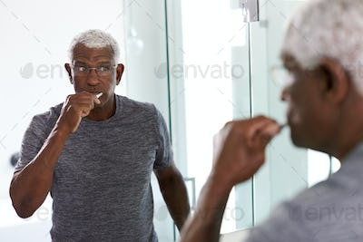 Senior Man Looking At Reflection In Bathroom Mirror Wearing Pajamas Brushing Teeth