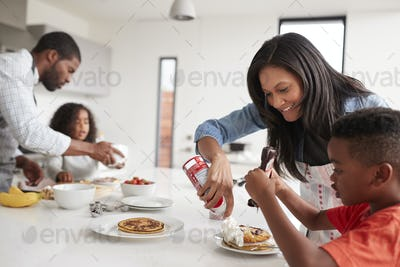 Family In Kitchen At Home Making Pancakes Together