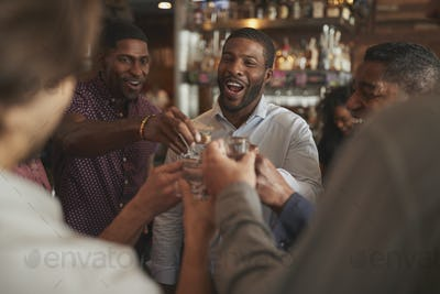 Group Of Male Friends On Night Out Drinking Shots In Bar Together