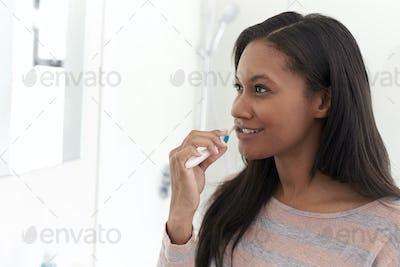 Woman Looking At Reflection In Bathroom Mirror Brushing Teeth