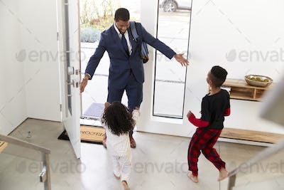 Children Greeting And Hugging Working Businessman Father As He Returns Home From Work