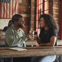 Young Couple Meeting In Sports Bar Making Toast Together