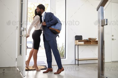 Woman Greeting And Hugging Businessman Husband As He Returns Home From Work