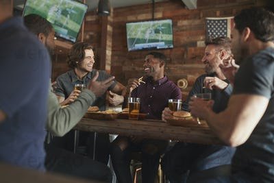 Male Friends Drinking Beer And Eating Burgers In Sports Bar