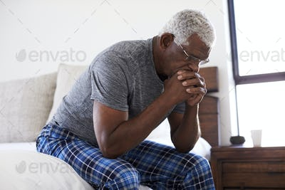 Depressed Senior Man Looking Unhappy Sitting On Side Of Bed At Home With Head In Hands