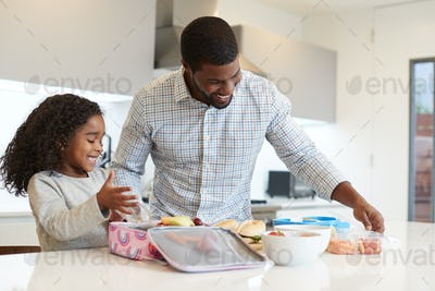 Daughter In Kitchen At Home Helping Father To Make Healthy Packed Lunch