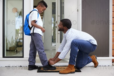 Father Tying Sons Shoelaces As He Leaves For School