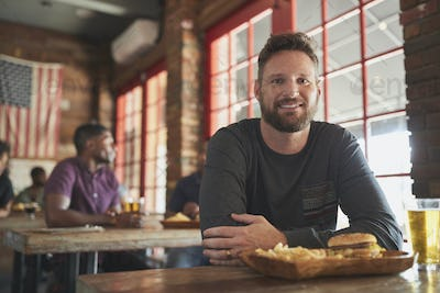 Portrait Of Man In Sports Bar Eating Burger And Fries