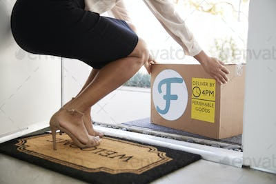 Close Up Of Woman Opening Front Door To Fresh Food Home Delivery In Cardboard Box Outside Front Door