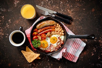 Delicious english breakfast in iron cooking pan
