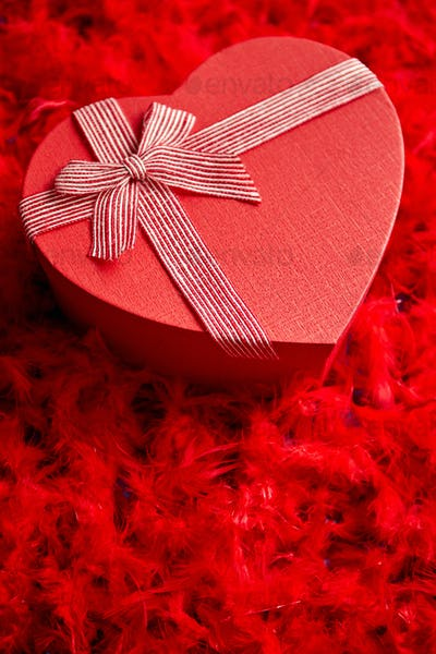 Heart shaped boxed gift, placed on red feathers background