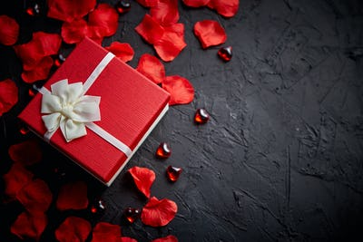 Gift box on black stone table. Romantic holiday background with rose petals
