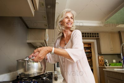 older smiling woman boiling water on kitchen stove top
