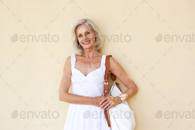 happy older woman standing in white dress with purse