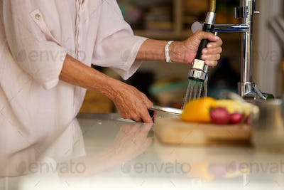 portrait of older woman washing vegetables in water