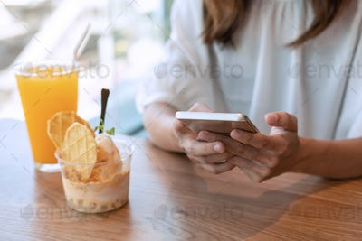 Young woman using smart phone and enjoy eating dessert in cafe