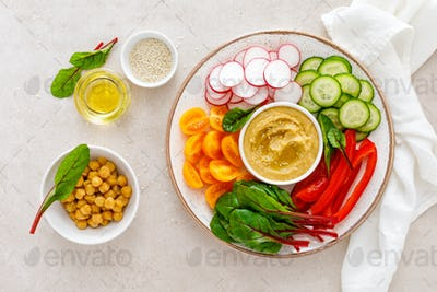 Vegetarian Buddha bowl with hummus and vegetables, top view