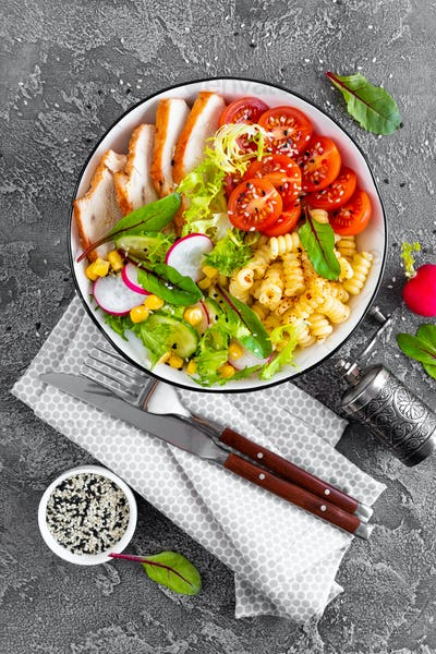 Grilled chicken meat with fresh vegetable salad and pasta