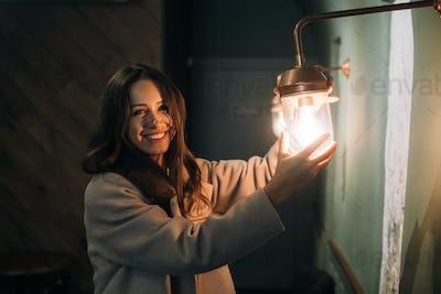Young beautiful woman holds in her hand a small wall lamp