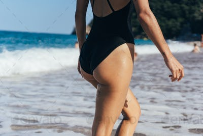 The girl in a black swimsuit by the sea. Back view