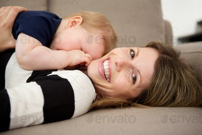 smiling woman lying on sofa with her baby son