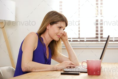 young woman sitting at desk looking at laptop screen