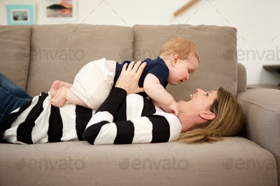 smiling mother lying on sofa at home and playing with her son