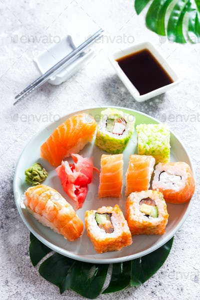 Various sushi on ceramic plate with metal Korean sticks on light stone background with green leaves