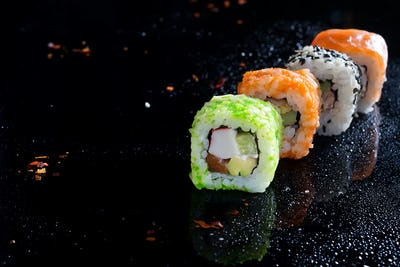 Colorful sushi sets with lots of sushi, roll . Stylish sushi sets on a black background with water