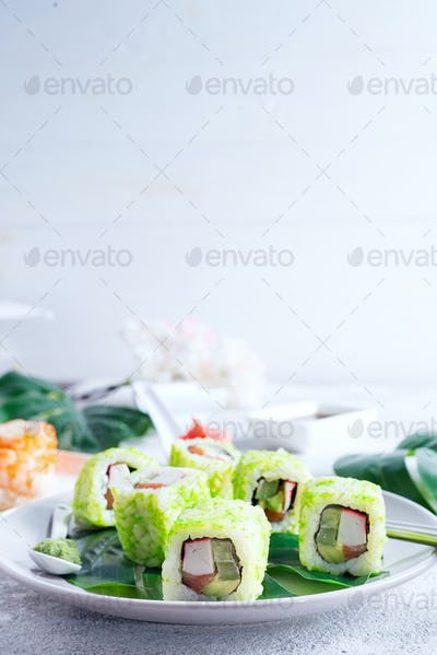 sushi roll with green caviar on a plate with chopsticks on stone background . Sushi menu. Japanese