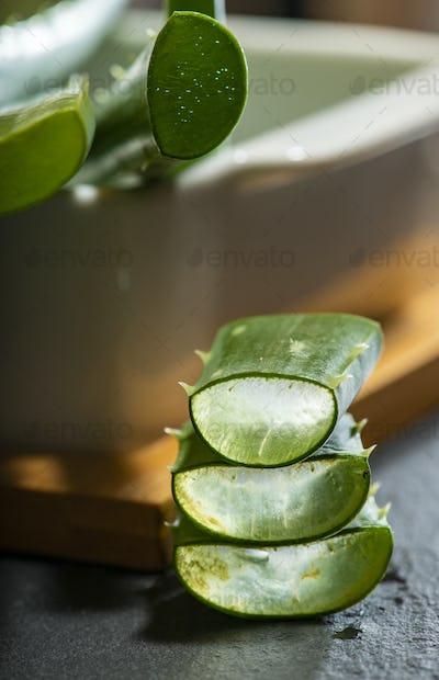 Aloe vera slices on dark background. Health and beauty concept.