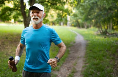 Attractive retired man with a nice smile jogging in park