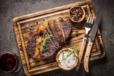 Grilled beef steak medium on wooden cutting board