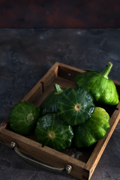 small size patty pan patisson squash in wooden box on dark wooden background with copy space