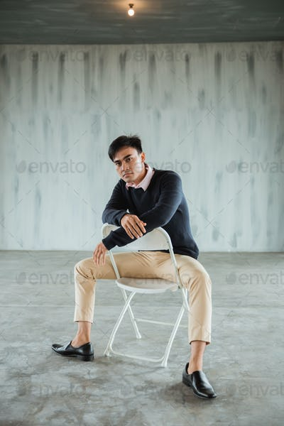 pose of a casual businessman sitting on a white chair in the hall