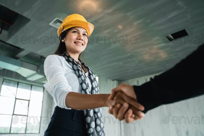 businesswoman with hardhat shaking hand