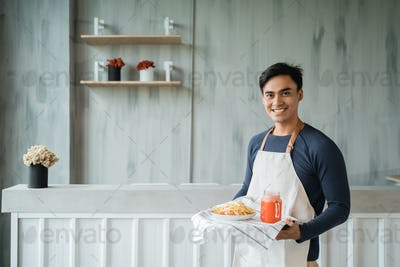 asian male waitress looking at camera and smiling