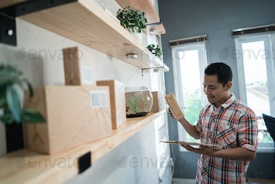 asian man worker hold and check a box to correct destination address