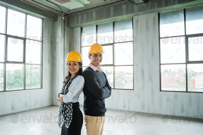 engineer team back to back folded hands standing in the hall wearing a safety helmet