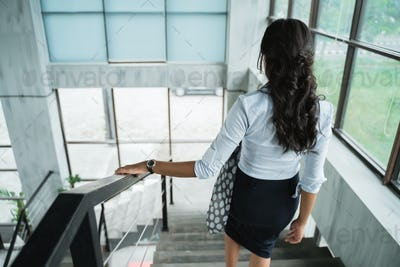 portrait from behind of businesswoman walking down stairs alone