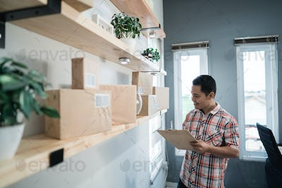 asian young worker look at boxes to checking item
