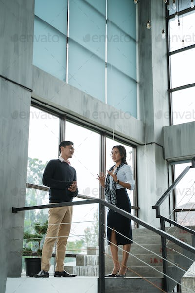 businessman and his partner talking about business on the stairs