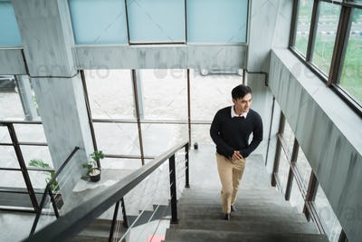 young asian businessman up the stairs enjoy situation