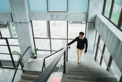 asian businessman walking up on the stairs go to his room in the upstairs