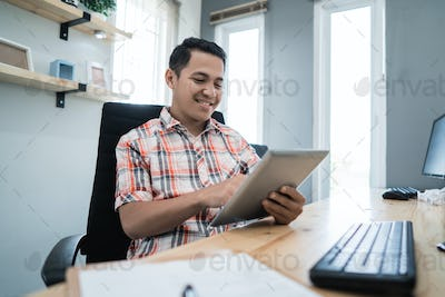 business owner relaxing using tablet at his office