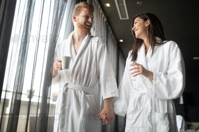 Happy young couple in white bathrobes drinking coffee together. Hotel, travel, relationships concept