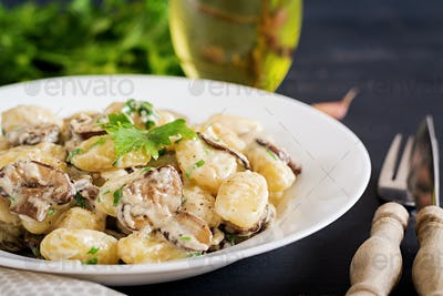 Gnocchi with a mushroom cream sauce and parsley  in bowl on a dark background