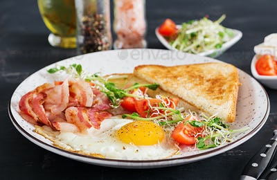 English breakfast - toast, egg, bacon and tomatoes and microgreens salad.