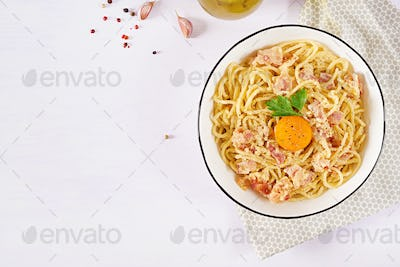 Classic homemade carbonara pasta with pancetta, egg, hard parmesan cheese and cream sauce.
