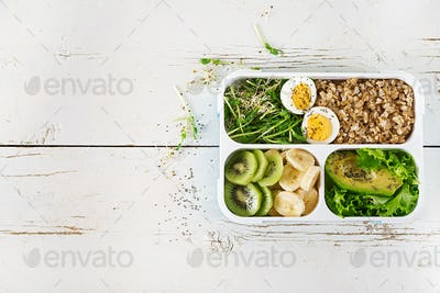 Lunch box  with boiled eggs, oatmeal, avocado, micro greens and fruits.